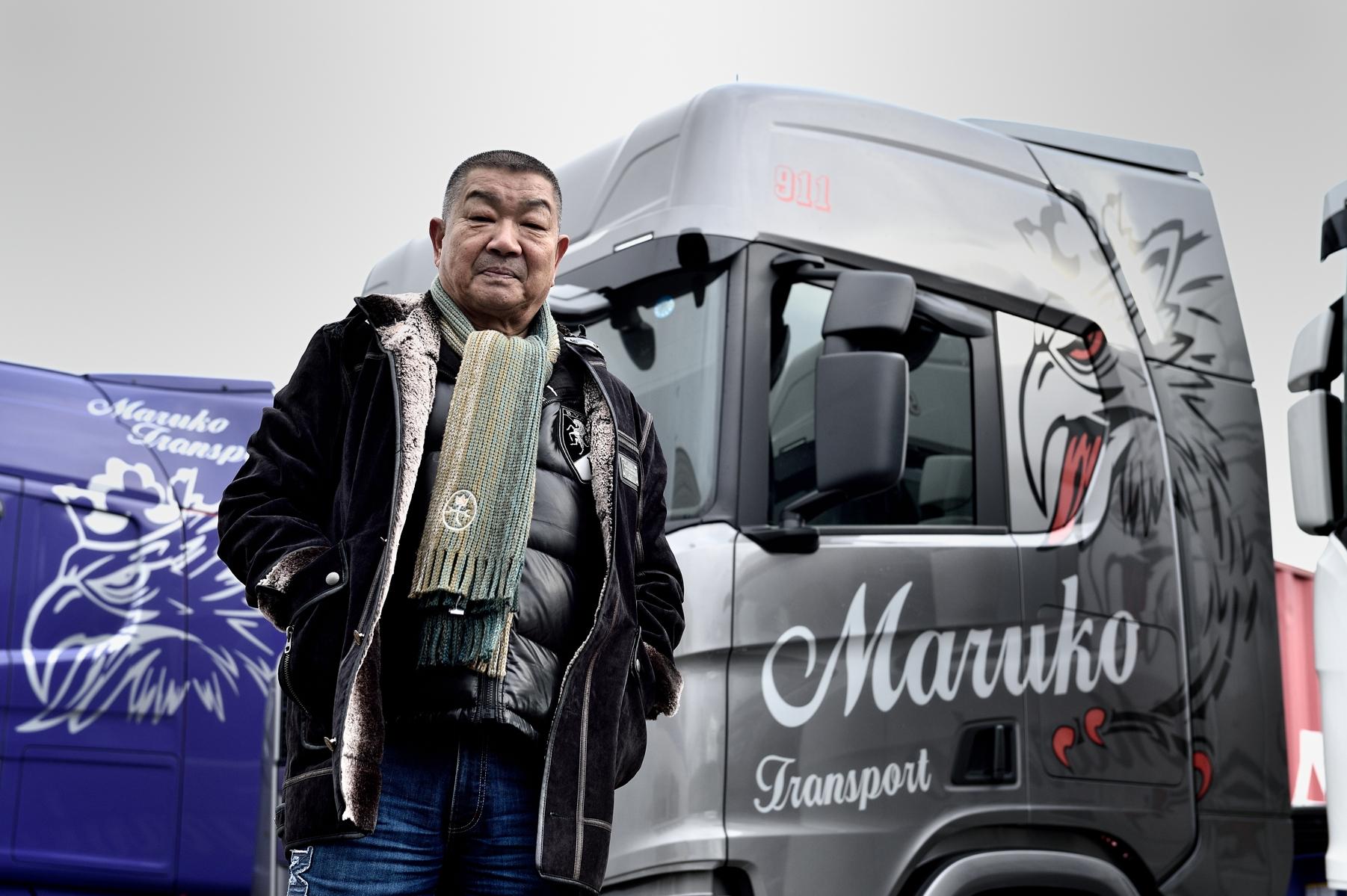 グレーで彩られたマルコートランスポートのスカニアトラックを背に立つ同社代表取締役の齋藤孝男氏